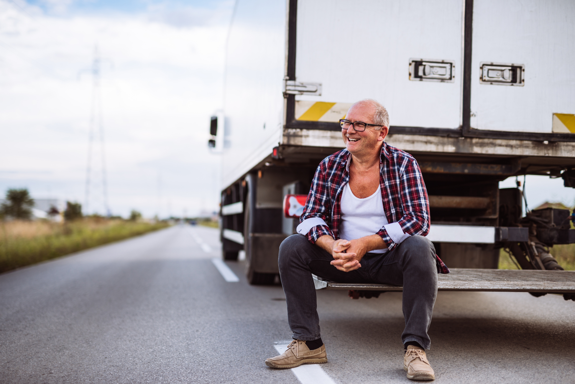 Senior truck driver posing next to his truck.